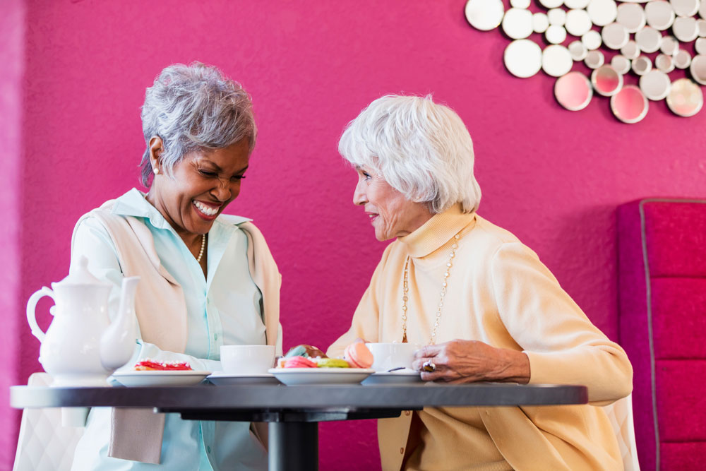 Two older women smile and share tea and snacks together at a table