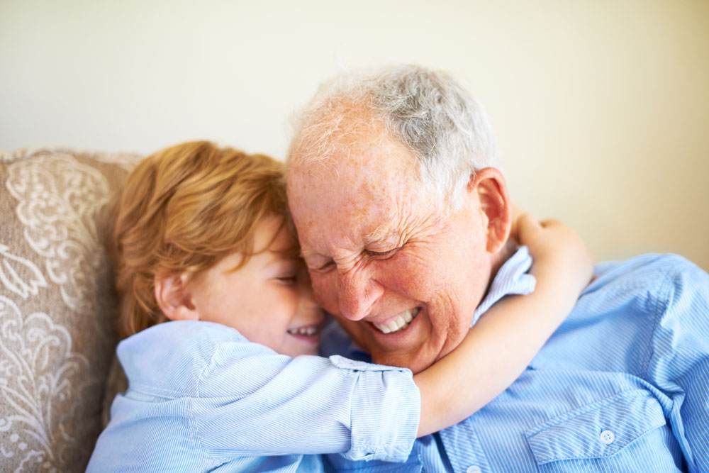 Young boy hugs older man while they both smile with their eyes closed