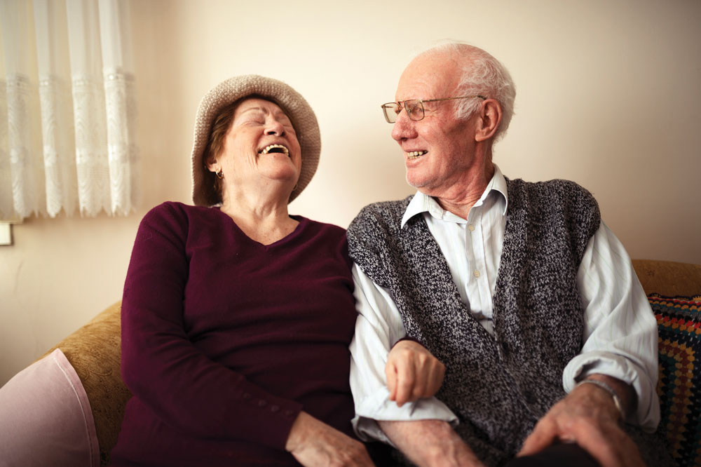 Airy Hills at North Bend Crossing senior male and female sit close together on couch and laugh