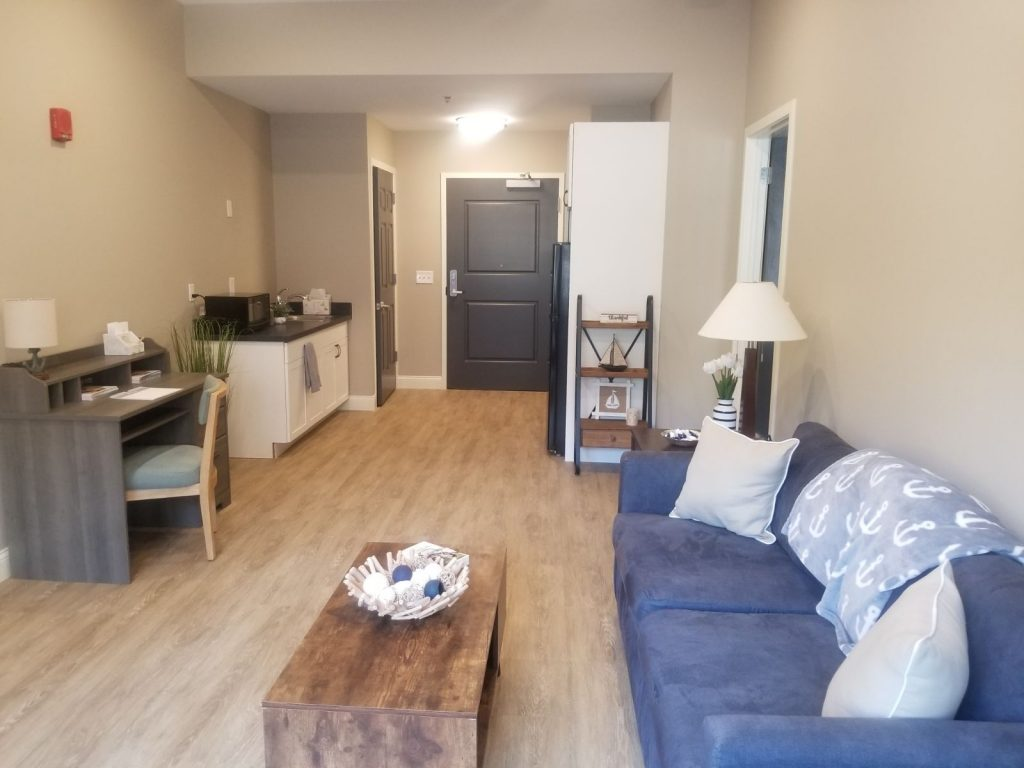 Image Gallery - Main living area with sofa, coffee table, desk, and kitchenette