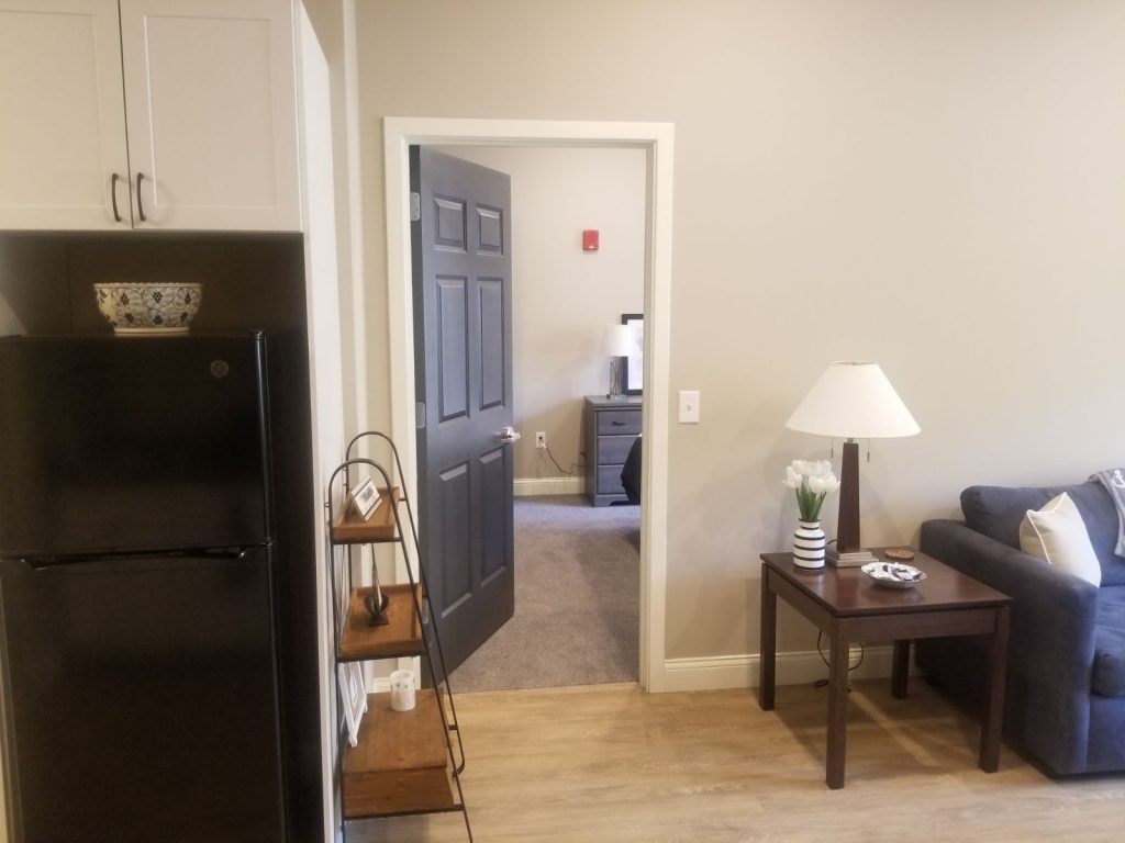 View of refrigerator, part of living area, and entrance to bedroom