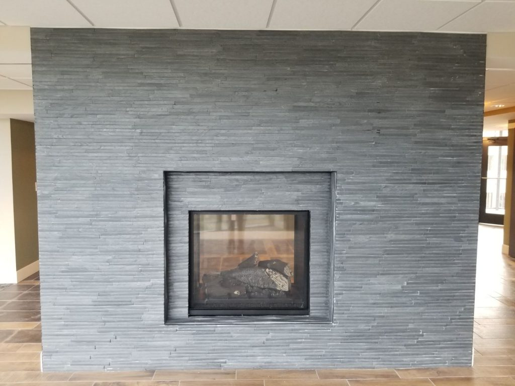 Closeup of large grey fireplace in lobby
