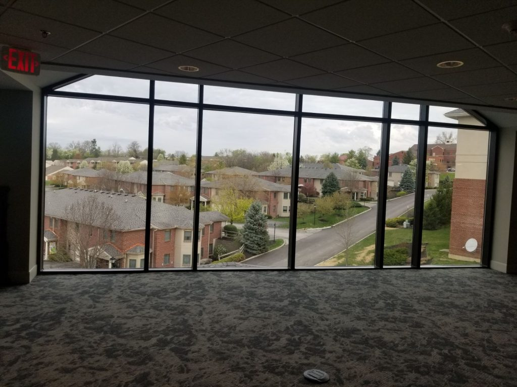 Large carpeted hallway space with floor to ceiling windows overlooking the community