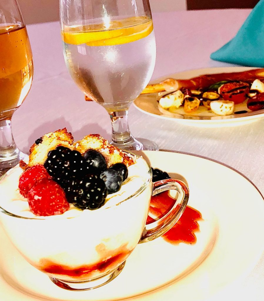 Closeup of yogurt parfait topped with fruit sitting next to several drinking glasses